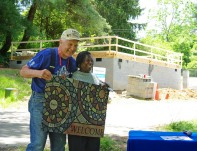 A Global Village volunteer presents Priscilla McDow with a signed welcome mat as a souvenir of their visit.